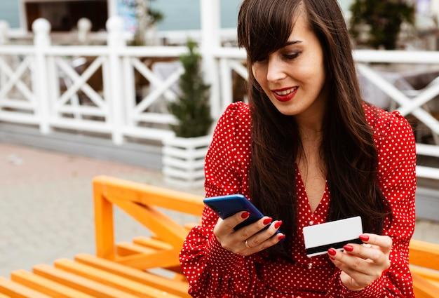 Vrouw die smartphone en creditcard gebruikt om online verkoop te winkelen