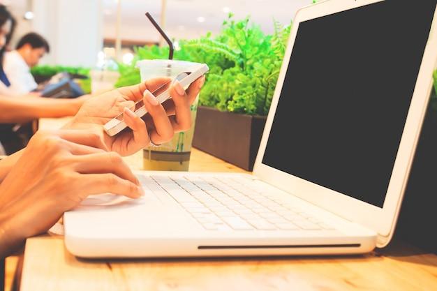 Vrouw die smartphone en laptop computer voor zaken gebruikt.