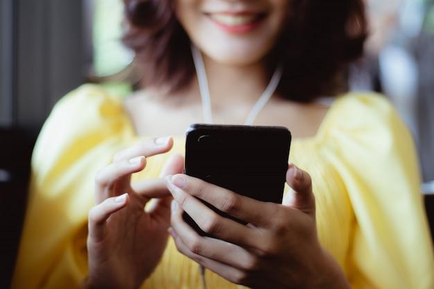 Vrouw die smartphone gebruiken die aan muziek in vrije tijd met gelukkig luisteren.