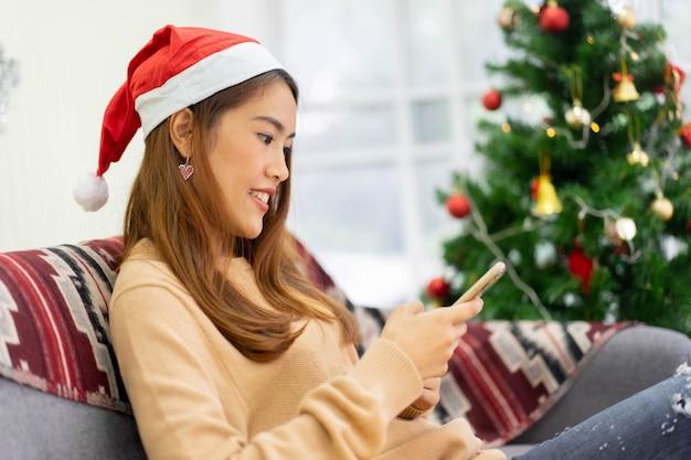 Vrouw die smartphone gebruikt om evenement op sociale media te controleren voor het concept van het kerstvieringsfestival