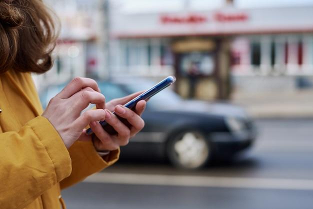 Vrouw die smartphone in de stad gebruiken