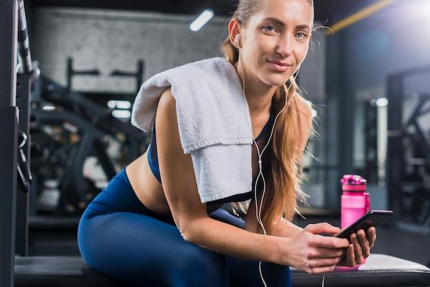 Vrouw die smartphone in gymnastiek gebruikt