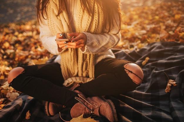 Vrouw die smartphone in herfst gebruikt. herfst meisje met slimme telefoongesprek in zon flare gebladerte. portret van kaukasisch model in bos in herfstkleuren