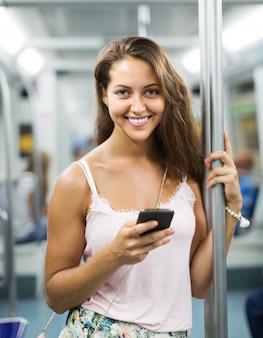 Vrouw die smartphone in metro gebruikt