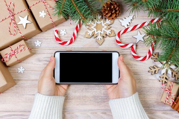 Vrouw die smartphone met het lege scherm, feestelijk trumpery frame, kerstmisgiftonderzoek, online het winkelen, seizoengebonden kortingen en verkoopconcept gebruiken