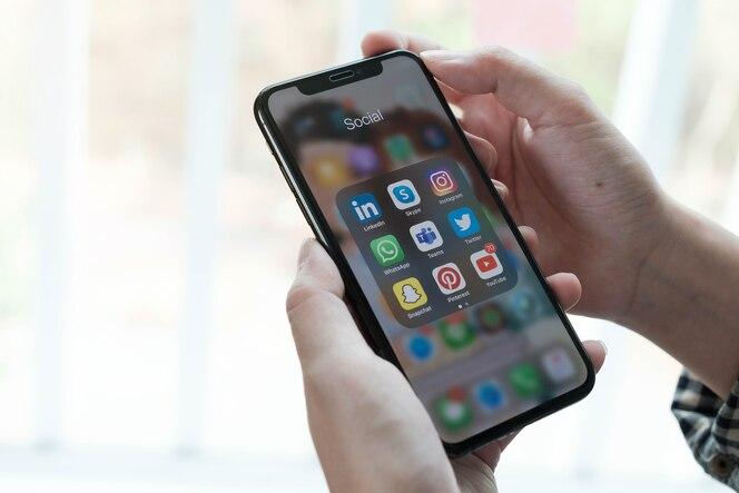 Vrouw die smartphone met pictogrammen van sociale media op scherm gebruikt