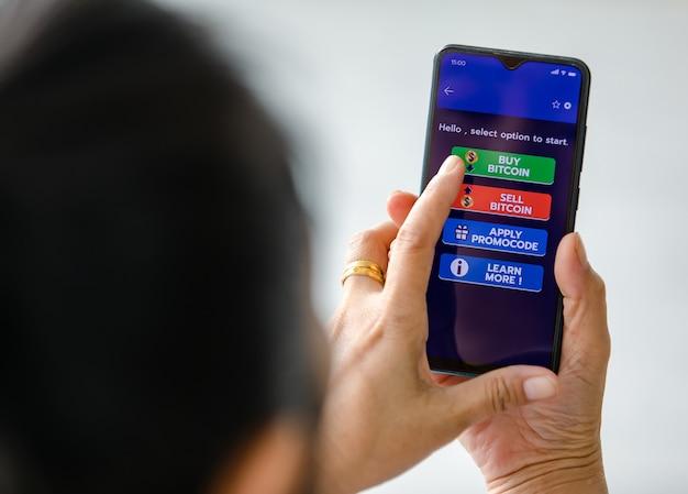 Vrouw die smartphones vasthoudt en vingeraanraking op het scherm gebruikt en selecteert op knoppen van koop- en verkoopapplicatie voor bitcoin of cryptocurrency digitale geldhandel.