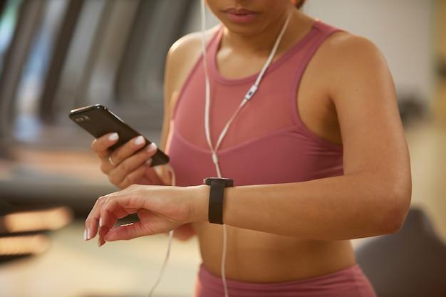 Vrouw die smartwatch in gymnastiekclose-up gebruiken