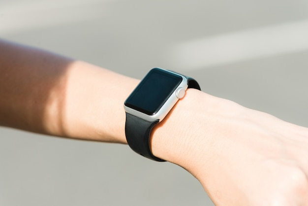 Vrouw die smartwatch met e-mailkengever gebruiken. smartwatch handapparaat informeert computer internetbericht