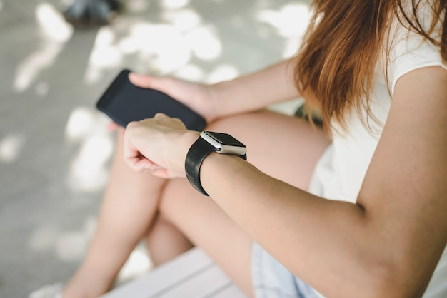 Vrouw die smartwatch met e-mailkengever gebruiken