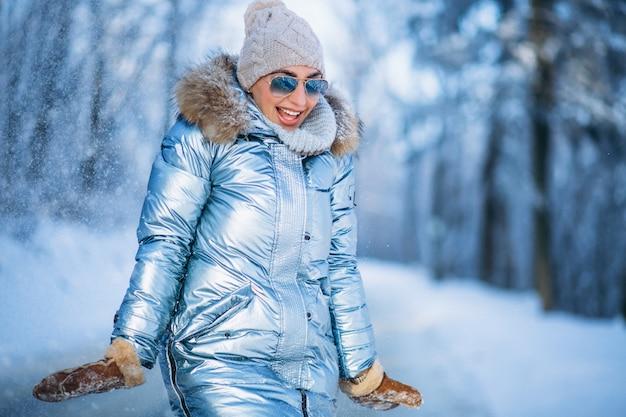 Vrouw die sneeuw in park werpt