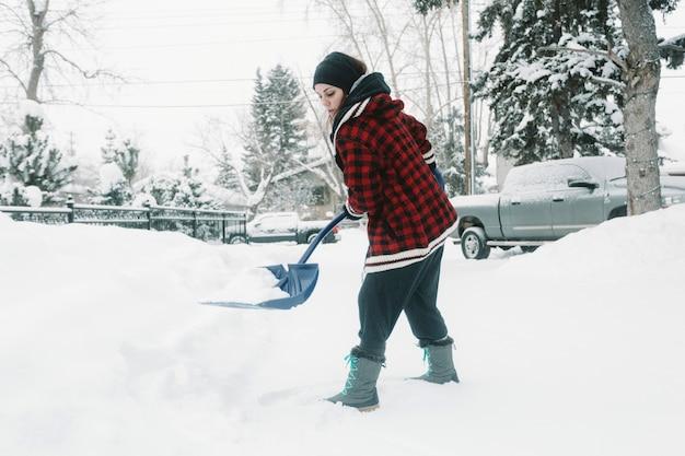 Vrouw die sneeuw op de achtergrond van pijnboombomen schept