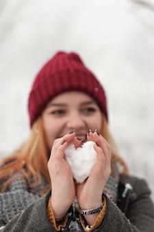 Vrouw die sneeuw vormt in hart