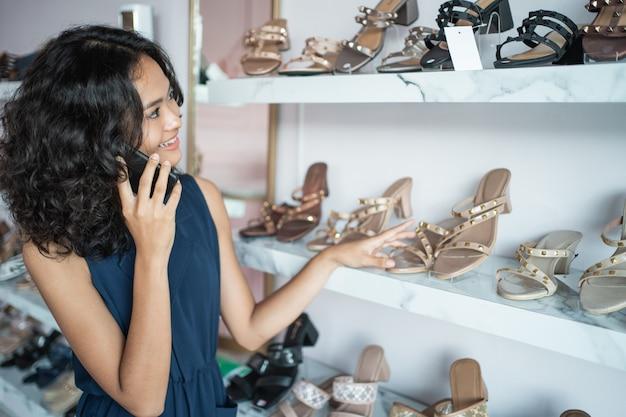Vrouw die sommige schoenen op de planken kiest op manier slaat op