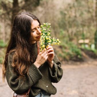 Vrouw die sommige wildflowers in aard houdt