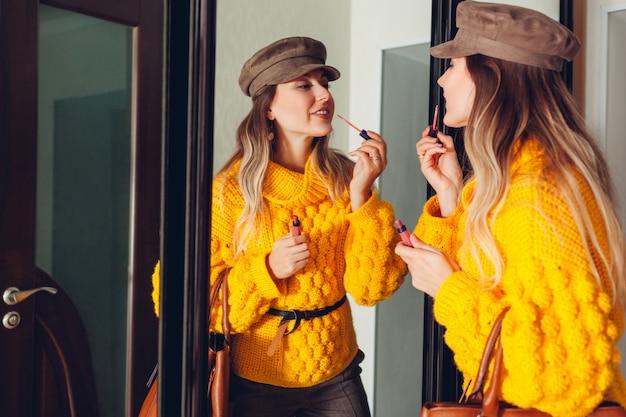 Vrouw die spiegel thuis bekijkt die modieuze sweater en toebehoren draagt en lippenstift toepast