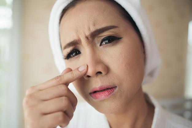 Vrouw die spiegel thuis bekijkt en haar gezicht controleert
