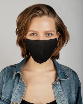 Vrouw die spijkerjasje en masker draagt