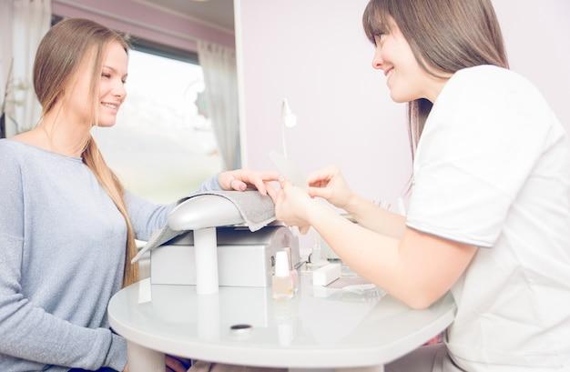 Vrouw die spijkersbehandeling in een schoonheidszaal maakt