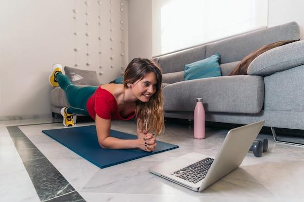 Vrouw die sporten op een mat doen die online klassen met laptop thuis volgen