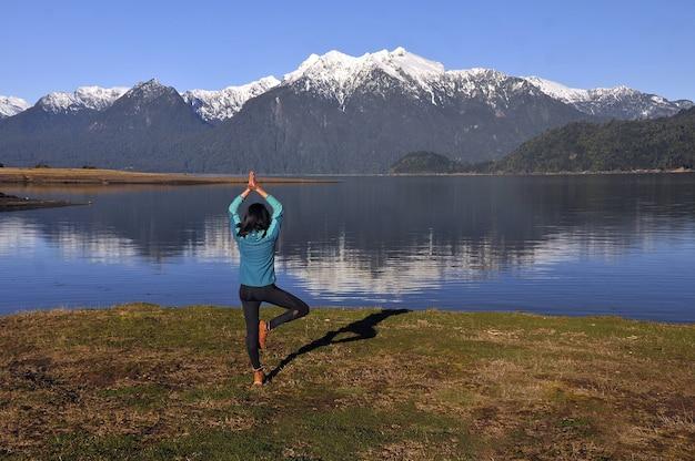 Vrouw die sportkleding draagt, een yogapositie houdt voor het kalme meer en de bergen