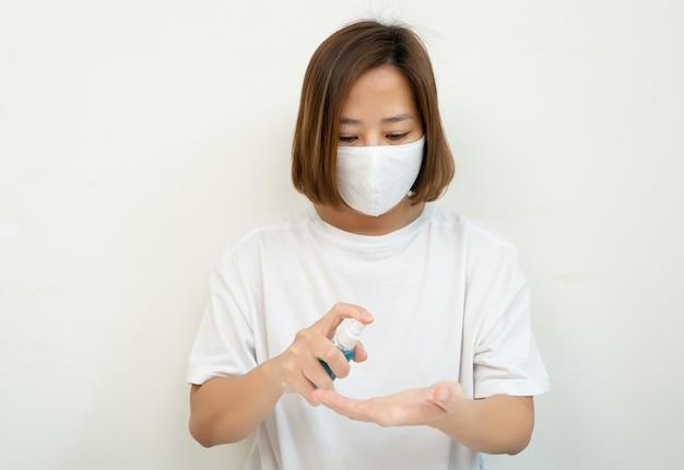 Vrouw die spray-desinfectiealcoholproduct op hand toepast, hand met alcoholdesinfecterend middel wast, het virus en bacteriën voorkomt