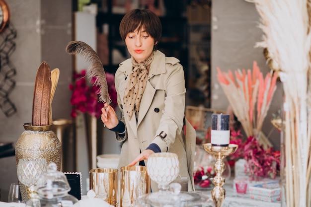 Vrouw die spullen in een decoratiewinkel koopt