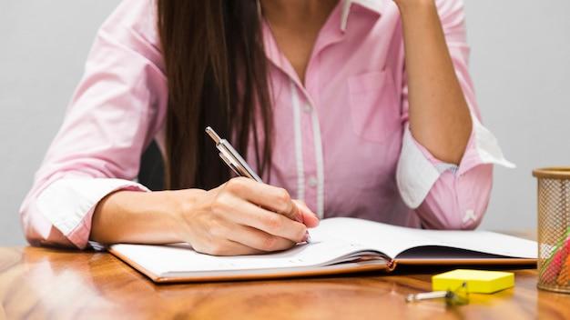 Vrouw die statistieken in agenda schrijft