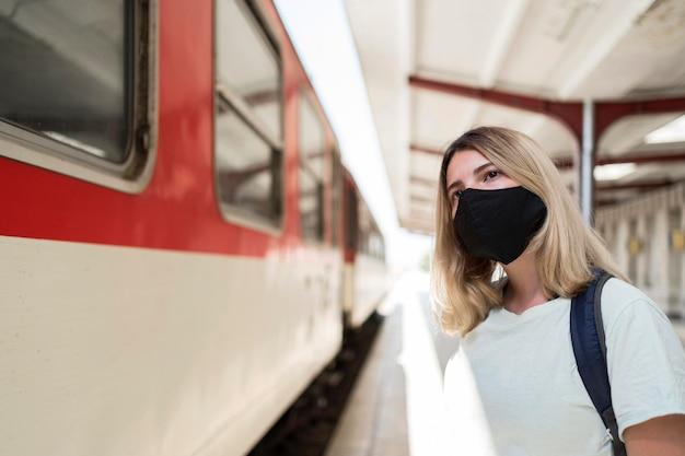Vrouw die stoffenmasker draagt dat zich naast de trein bevindt