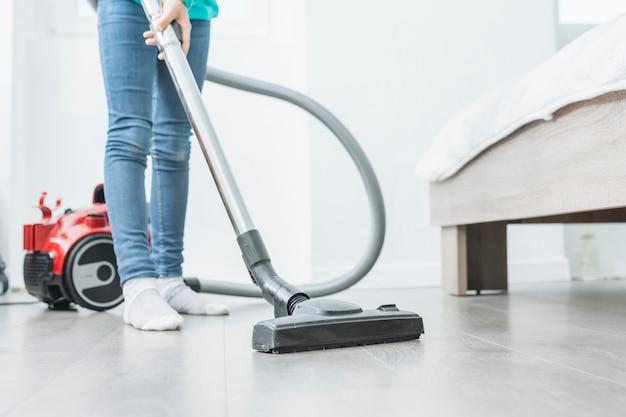 Vrouw die stofzuiger thuis met behulp van