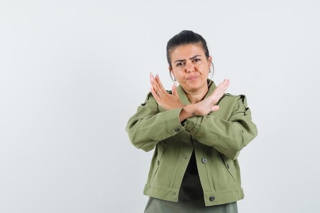 Vrouw die stopgebaar in jasje, t-shirt toont en resoluut kijkt