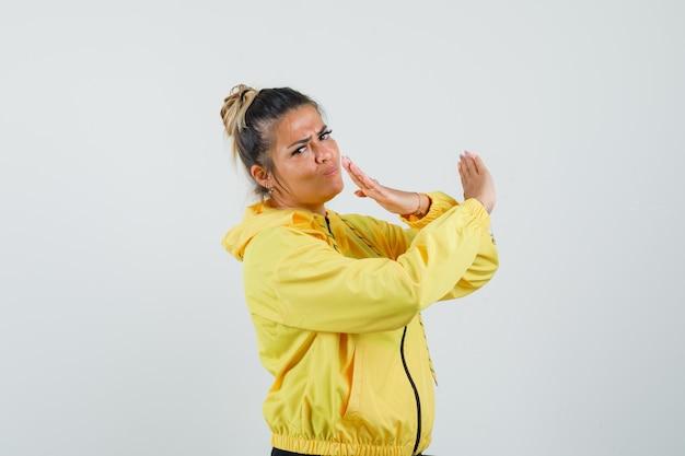 Vrouw die stopgebaar in sportkostuum toont en ernstig, vooraanzicht kijkt.