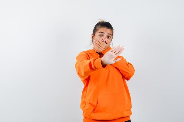 Vrouw die stopgebaar toont, hand op mond houdt in oranje hoodie en bang kijkt