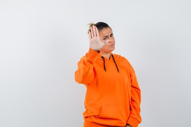 Vrouw die stopgebaar toont in oranje hoodie en er serieus uitziet?