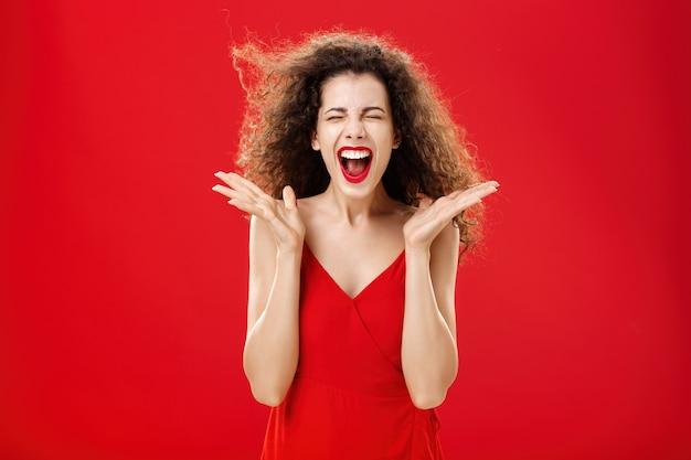 Vrouw die stress loslaat en hardop schreeuwt expressieve en overgevoelige aantrekkelijke vrouw met krullend haar in...