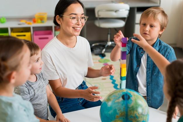 Vrouw die studenten leert spelen met kleurrijke toren
