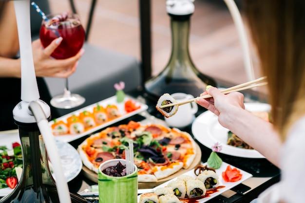 Vrouw die sushi met eetstokje nemen dat voor diner wordt gediend