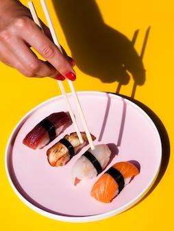 Vrouw die sushi neemt vormt een grote roze plaat