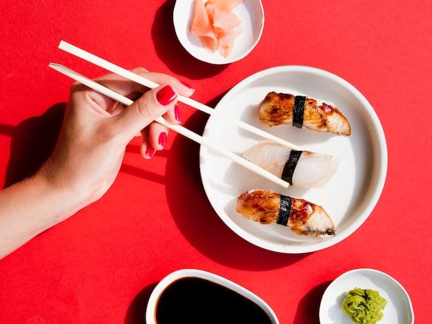 Vrouw die sushi van witte plaat plukt