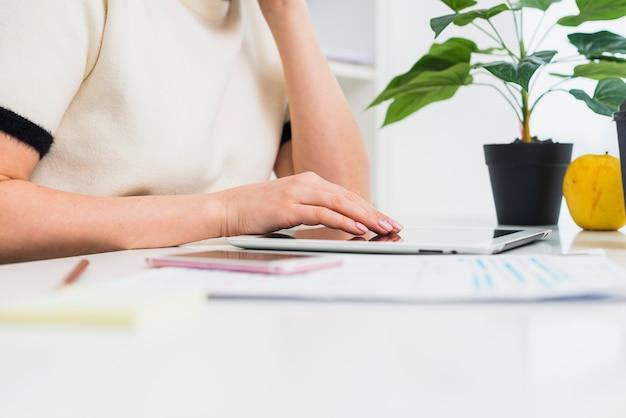Vrouw die tablet gebruiken bij lijst in bureau