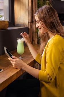 Vrouw die tablet gebruikt en milkshake drinkt