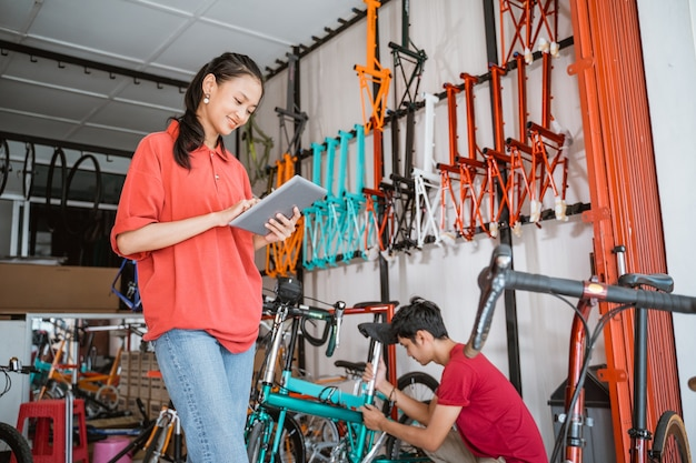 Vrouw die tablet gebruikt tegen een fietsframe in een winkel