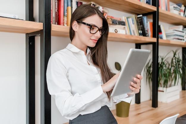 Vrouw die tablet in het bureau gebruikt