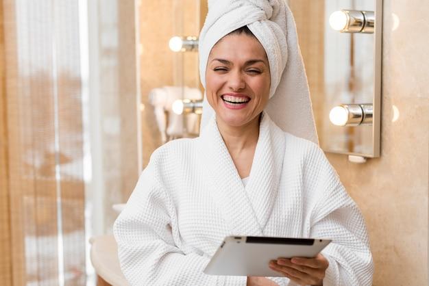 Vrouw die tablet in hotelruimte gebruikt