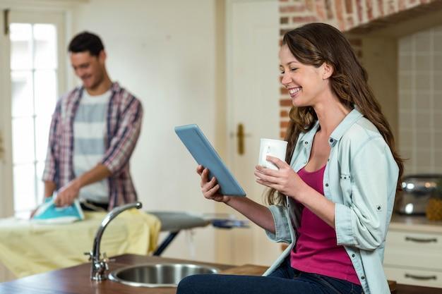 Vrouw die tablet in keuken gebruiken terwijl mens die een overhemd op achtergrond strijken