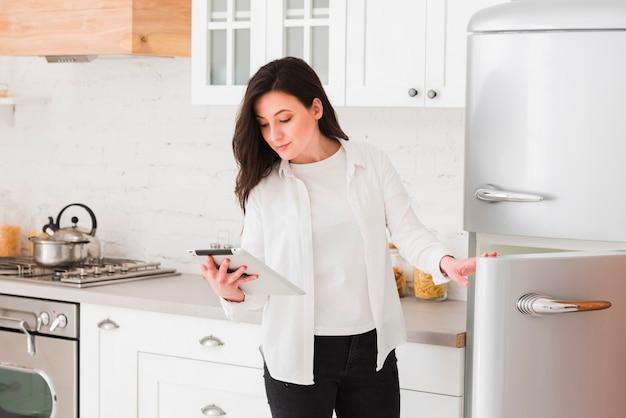 Vrouw die tablet voor ingrediënten bekijkt