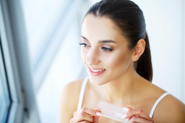 Vrouw die tanden gebruiken die strook voor mooie witte glimlach witten