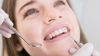 Vrouw die tanden heeft die bij tandartsen worden onderzocht