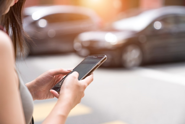 Vrouw die taxi app op mobiele telefoon gebruiken