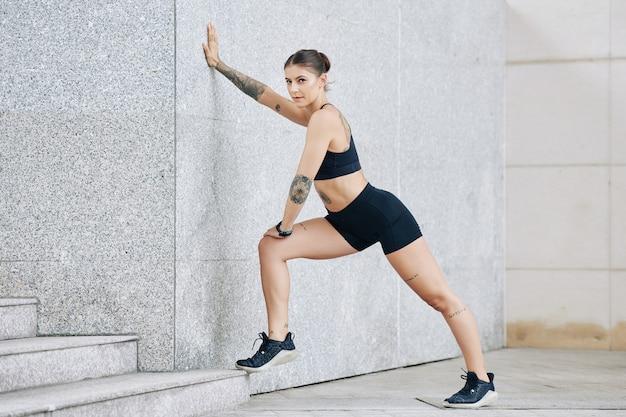 Vrouw die tegen de muur leunt bij het strekken van het been na het hardlopen op straat
